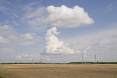 Unique cloud in the form of a large mushroom on a blue sky. Photo on the white clouds bizarre over arable land stock illustration