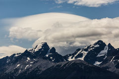 Unique Cloud Formation Over Rugged Snowy Mountain Range Stock Images