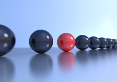 Unique concept. Red sphere in a row with black spheres. Depth of field is set on red sphere Royalty Free Stock Images