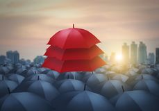 Unique concept, leadership, uniqueness, red umbrella among grey umbrella. Unique red umbrella among black umbrellas with city background, leadership concept stock image