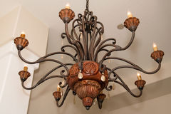 Unique Custom Made Ceiling Light Fixture. A one-of-a-kind custom made copper metal and carved wood indoor ceiling light fixture royalty free stock photos