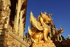 A unique design golden typical Thai style lion statue stands out from the blue sky in central region of Thailand. Very beautiful and eye catching in a temple royalty free stock image