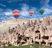 Unique geological formations in Cappadocia, Anatolia, Turkey. Panorama of unique geological formations and colorful hot air balloons flying over Zelve valley in Royalty Free Stock Photos