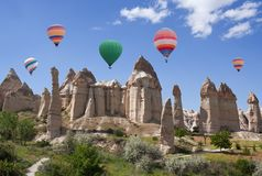 Unique geological formations in Cappadocia, Anatolia, Turkey. Panorama of unique geological formations and colorful hot air balloons flying over Love valley in Royalty Free Stock Photos
