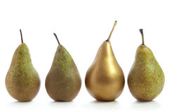 Unique. Gold pear standing out in a row of fruit over a white background Royalty Free Stock Images