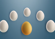 Unique golden egg between white eggs. On blue background Stock Images