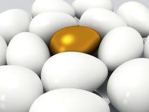 Unique golden egg among white eggs Royalty Free Stock Photo