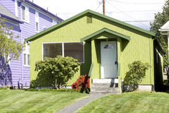 Unique green house. The smallest house stood out in the block because of its unique eye-catching green colors. This house was for sale Stock Photo