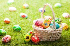 Unique hand painted Easter eggs in basket on grass Stock Photos