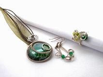 Unique handmade jewelry made of silver wire and green glass. Taken in the Golden City of Pforzheim, Germany stock photography