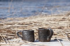 Unique handmade two cups with folk sign with blurred lake on background. Beautiful closeup of unique handmade two cups with folk signs with blurred lake on Stock Images