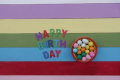 Happy Birthday text with multi colored wooden letters and chocolates. Unique Happy Birthday celebration card with a creative composition of multi colored wooden royalty free stock images