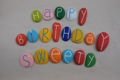 Happy Birthday Sweety with colored stones over white sand