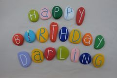 Happy Birthday Darling with colored stones over white sand