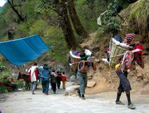 A UNIQUE HUMAN LABOUR. Pilgrims are being lifted by porters on their backs on the mountain slops of Himalayas, India Royalty Free Stock Photos