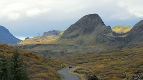 Unique icelandic landscape with lava field, hills, winding road and moving car, in autumn day. With sunshine on a part of shot stock footage