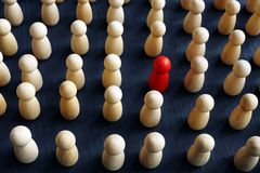 Unique, individual and think differently. Crowd of wooden figures. And red one royalty free stock image