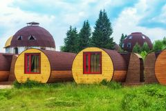 Unique lodgings blend in with nature. Eco housing. House-barrel outdoors. stock image