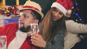 Unique man celebrating Christmas after hard work by Santa Claus. New Year party with beautiful girlfriends, making selfie by mobile phone and drinking stock video