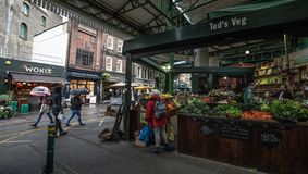Borough market in central London with colorful kiosks and stalls on a rainy day. stock photography