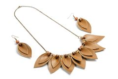 Unique pendant and earrings consisting of petals of brown leather on a white background.  Royalty Free Stock Images
