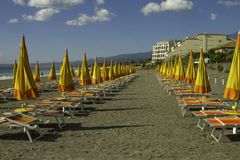 Unique perspective of colorful parasol and deck chairs on the ocean front of Giardini di Naxos in Sicily in a blue sky day. Unique perspective of colorful closed royalty free stock image