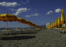 Unique perspective of colorful parasol and deck chairs on the ocean front of Giardini di Naxos in Sicily in a blue sky day. Unique perspective of colorful royalty free stock photography