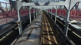 View of Subway Train Traveling on Williamsburg Bridge. A unique perspective of looking down at the J-train as it passes directly underneath a pedestrian on the stock video footage