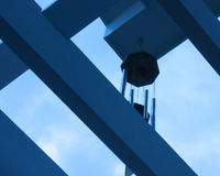 Unique Perspective. Photo taken looking up through a pergola to the wind chimes and sky beyond stock image