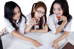 Unique perspective of students in a discussion. Unique perspective of three beautiful female students studying together on desk royalty free stock photo