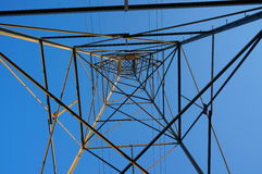 Unique Perspective Transmission Tower Patterned Against Sky. A view from the ground up into the metal and wire frame of an electrical transmission tower, forming royalty free stock image