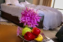 Fruit bowl in a hotel in a romantic scene. This unique photo shows a fruit basket with an orchid and a ruffled bed in a hotel room in the background stock photos