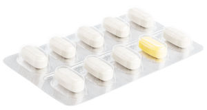 Unique pill shining between white tablets Stock Photography