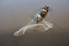 Unique posture's fisherman when cast a net. AN GIANG, VIET NAM- NOV 13: Nice, unique posture of fisherman when he cast a net from wooden boat on river in An royalty free stock photography