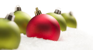 Unique Red Amongst Green Christmas Ornaments on Snow stock images