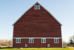 Unique red barn. Green grass and blue sky on an old farm Royalty Free Stock Photos