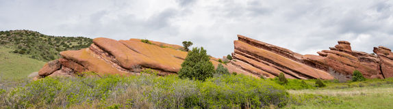 Unique red rock formation with green bushes and clouds Royalty Free Stock Photography