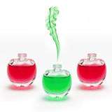 Unique Scent. Green smoke rising from little scent bottle between two other red ones stock photos