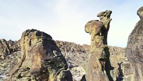Bare rock pinnacle rises above a desert canyon floor