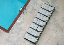 Unique shot of pool with lounge chairs. Pretty blue pool and chase lounge chairs photographed from above Royalty Free Stock Image