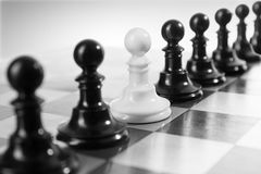 Unique. Single little pawn among many different others Royalty Free Stock Photo