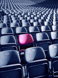 Unique Stadium Seat. Uniqueness concept represented by red-pink colored stadium seat. There's no one like you Stock Photography