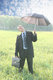 A unique view of a businessman. Standing on meadow , holding an umbrella on a bright sunny day, reaching out with his hand as it to check to see if it is Stock Images