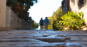 Unique view of the medieval cobblestone streets from paving stones. Blurred silhouettes of people away. Croatia Stock Photos
