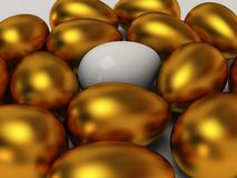 Unique white egg among gold eggs Stock Photography