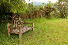 Unique Wooden Bench in a meadow. A uniquely shaped wooden bench sits in an open meadow Stock Photo