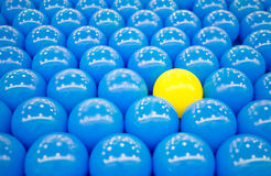 Unique yellow ball among blue balls Stock Image