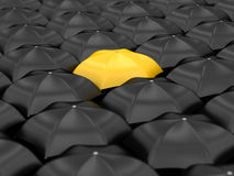 Unique yellow umbrella. With many black umbrellas Stock Photo