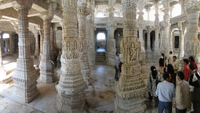 Uniquely carved columns in the mandap. RAJASTHAN, INDIA - DEC 4 -Indian visitors tour the Jain temple  on Dec 4, 2009, in Ranakpur,  Rajasthan, India Royalty Free Stock Photography