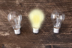 Uniqueness and individuality concept. Lightbulb glowing among the others. Uniqueness concept Royalty Free Stock Images